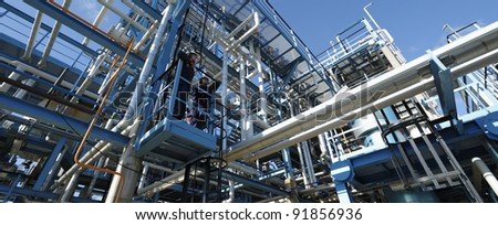 two workers standing on landing, large pipeline construction as seen inside oil and gas refinery, panoramic view - stock photo