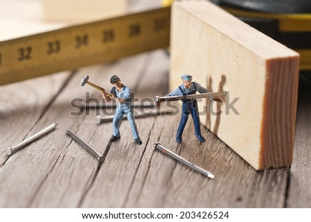 Two workers sticks nail. The concept of teamwork.  - stock photo