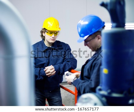 Two workers talking about a job in a factory, controls the operation of devices in a power plant. Shallow Doff. Authentic fluorescent light.