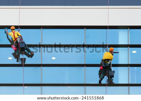 Two workers washing windows of the modern building. - stock photo