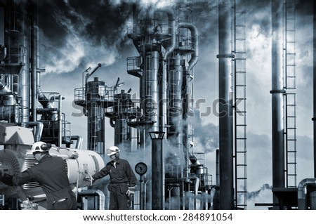 two workers with pipelines machinery, smoke, smog and industrial refinery in background - stock photo