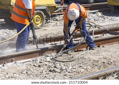 Two Workers with pneumatic hammer drill equipment breaking Concrete at construction site  - stock photo