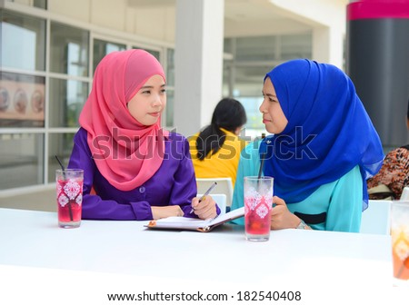 two working muslim woman have discussion at university cafe