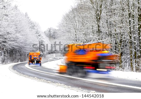 Two working snow plows on winter road, vehicles blurred - stock photo