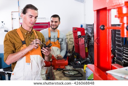 Two workmen toiling in a locksmiths workshop and smiling  - stock photo