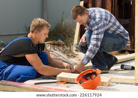 Two workmen working on a building site measuring insulation panels for installation at the corner of a new build house - stock photo
