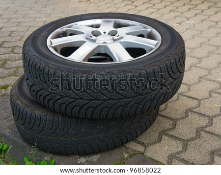 Two worn old tires with discs lying on the road - stock photo