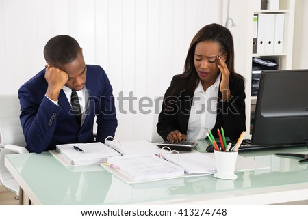 Two Worried African Businesspeople Sitting In Office - stock photo