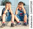 Two worried schoolboys sitting in front of their school. - stock photo