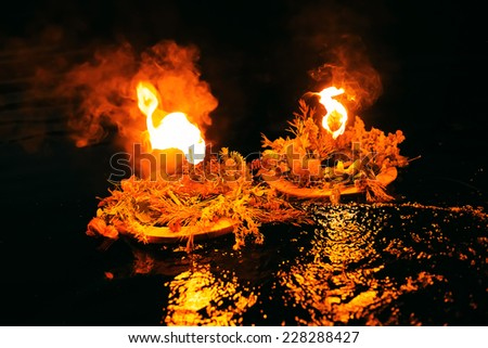 two wreaths burning with reflactions on water