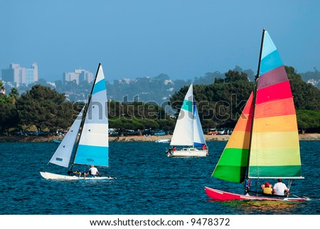 Two yachts and a catamaran are sailing in a Mission Bay, California on a nice summer afternoon.