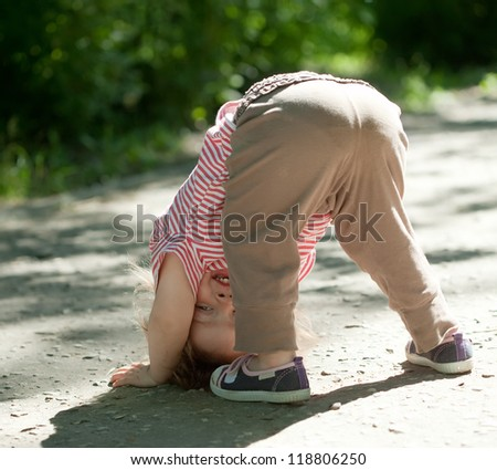 Two-year baby girl playing upside down in street - stock photo