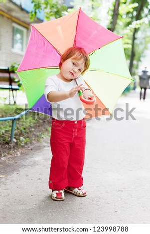 Two-year baby girl with umbrella in summer