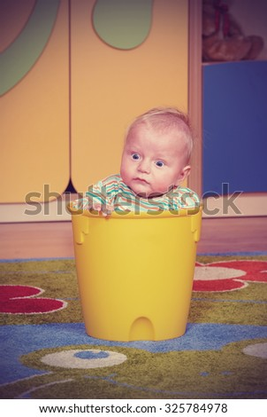 Two-year boy in a bucket on a colored carpet in the nursery - stock photo