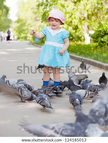 two-year girl feeding pigeons  in the city street