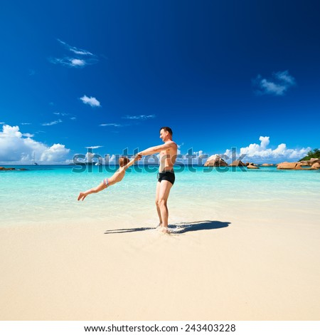 Two year old baby boy and his father playing on beach at Seychelles - stock photo