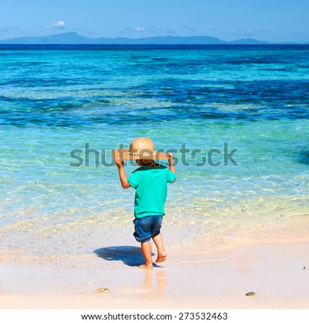 Two year old baby boy playing on beach at Seychelles