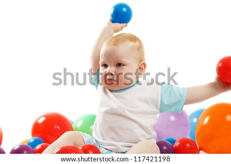 Two year old boy in a pool of colored balls - stock photo