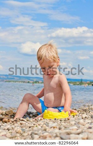 Two-year old boy playing on the beach.