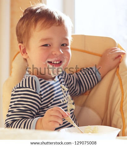 Two year old boy smiles to the camera eating porridge. - stock photo