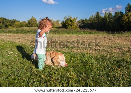 Two year old girl and a labrador retriever in a field of grass