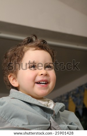Two year old girl is laughing during haircut at home - stock photo