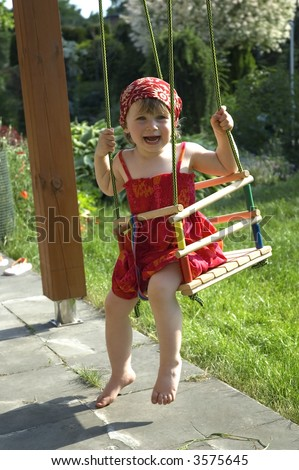 two-year-old girl on a swing in the garden