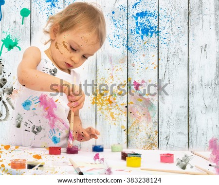 two-year old girl paints with poster paintings. - stock photo