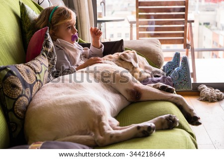 Two year old girl stroking her dog and sitting in the sofa at home - stock photo