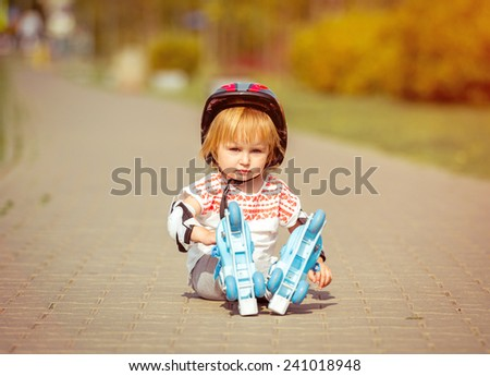two year old pretty girl in roller skates and a helmet sitting on the street - stock photo