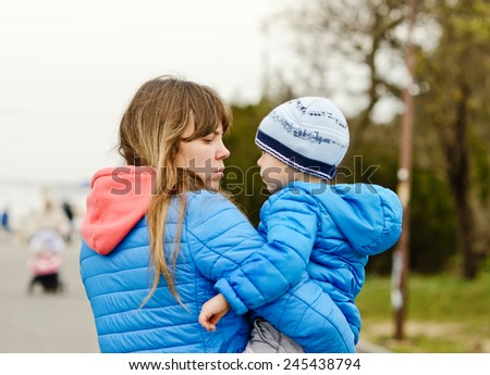 two-year-old toddler boy on the mother's hands - stock photo