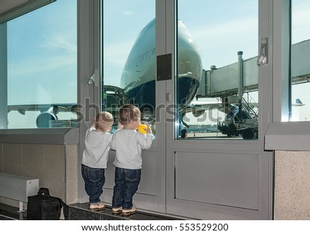 Two-year-old twins wait at airport. Kids look out of window aboard plane. Expectation of travel family with children.