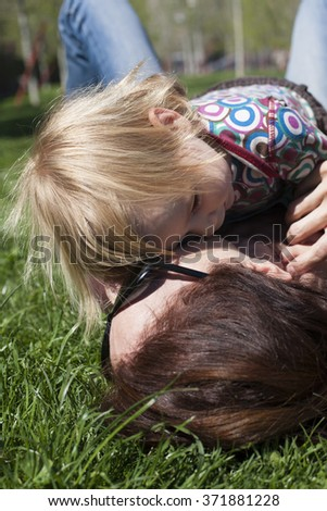 two years aged blonde baby colored shirt hugging with brunette woman mother with black sunglasses lying on green grass lawn - stock photo