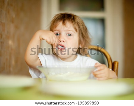 two-years child himself eats from plate  with spoon