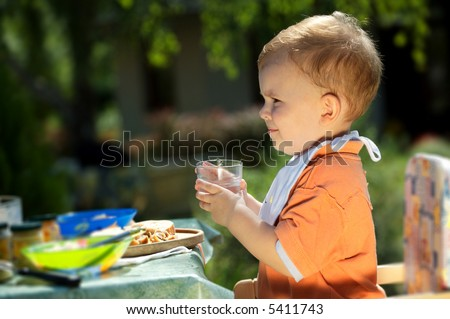 Two years old baby boy drinking. Family BBQ party outdoor, in the garden.