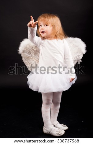 Two years old baby girl wearing white angel wings over black background. - stock photo