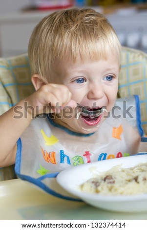 two-years-old blond boy enjoys his pasta - stock photo