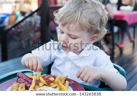 Two years old boy eating french fries in summer, outdoors - stock photo