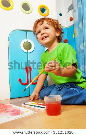 Two years old boy painting holding and dipping paintbrush into water bucket with smile on his face - stock photo