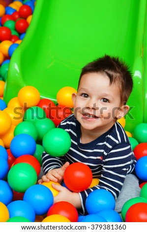 Two years old boy sitting on plastic balls by a slide - stock photo