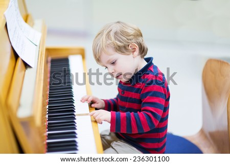 Two years old funny positive toddler child playing piano. Early music education for little kids. child at school, learning music instrument. - stock photo
