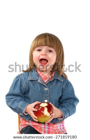 Two years old girl in a blue jacket trying to eat an apple - stock photo