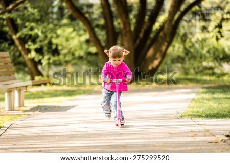 Two years old girl riding her scooter on the park - stock photo