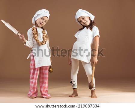 Two 5 years old girls bakers studio shot - stock photo