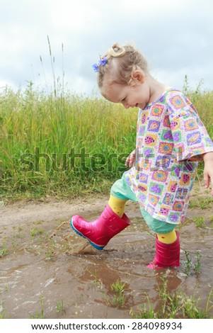 Two years old preschooler girl is having fun walking summer field puddle - stock photo