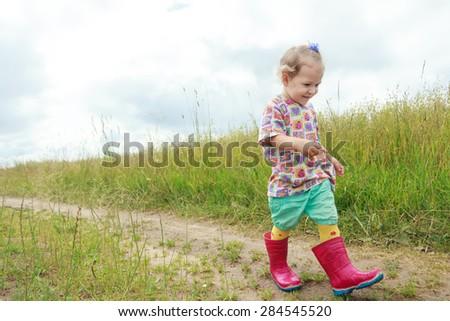 Two years old preschooler girl is walking by foot on farm field summer dirt road - stock photo