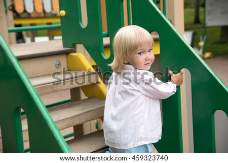 Two years old pretty blonde girl go up stairs in children playground - stock photo
