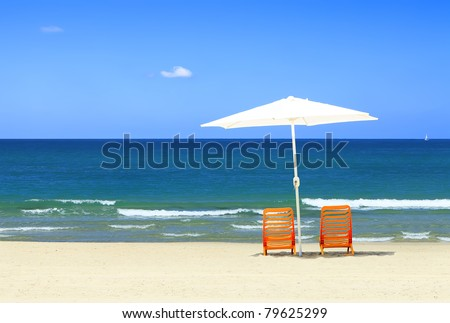 Two yellow chairs under a white umbrella on a sandy beach of Mediterranean sea