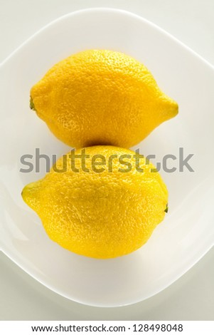 Two yellow lemon on a plate  and the white background - stock photo