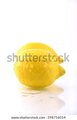 Two yellow lemon on the glass surface. Lemons on a white background.